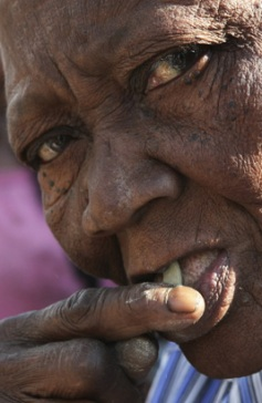 A woman tests a mud cookie before buying them at La Saline market in Port-au-Prince, Jan. 25, 2008.