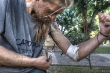A drug addict shots up narcotics in a public park in the center of Athens. Since 2010 drug use has risen by 20%.