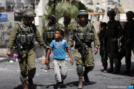 Israeli soldiers arrest a young Palestinian boy following clashes in Hebron, on June 20, 2014