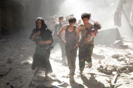 Σύρια γυναίκα και μικρά παιδιά φεύγουν από ένα βομβαρδισμό στο Alep με ένα τραυματισμένο παιδί στα χέρια, 26 Ιουνίου 2014